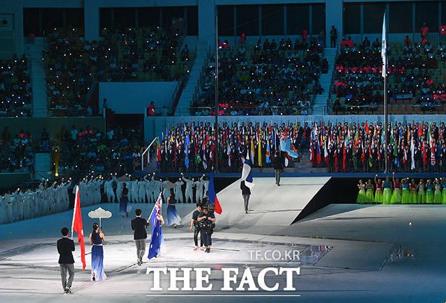 참가국들의 국기가 차례대로 입장하고 있다.