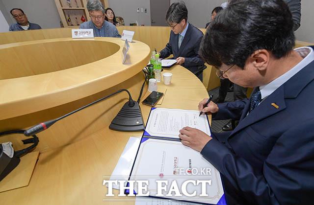 협약서에 서명하는 신중철 이사와 고종호 회장, 서형주 교수