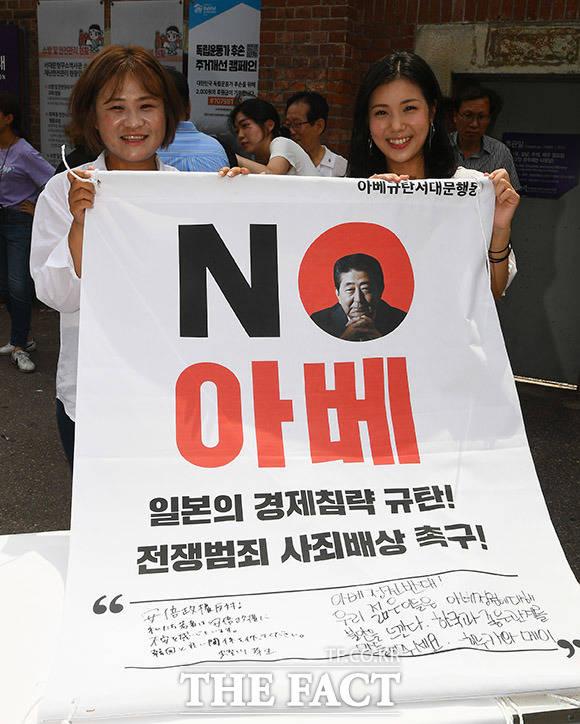 일본인 관광객 히루카와 메이(오른쪽) 씨가 아베 정부를 규탄하는 문구를 서명한 뒤 기념촬영을 하고 있다.