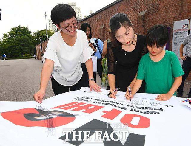 오는 10일 설치되는 현수막에 일본정부에 대한 항의 문구를 서명하는 참가자들