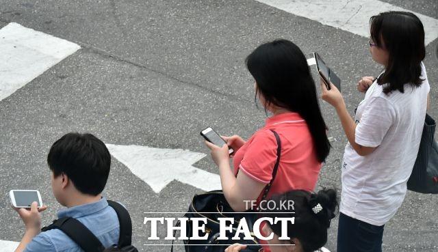 스마트폰으로 거리에서 영상을 시청하는 시민들. /더팩트DB