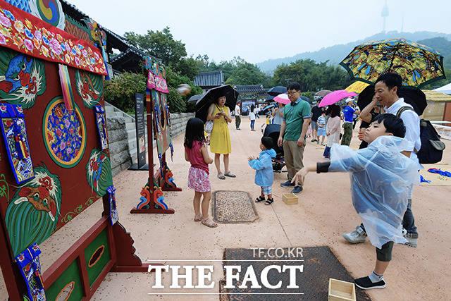 추석 연휴 셋째 날인 14일 서울 중구 남산골한옥마을을 찾은 어린이들이 우비를 입고 전통 민속놀이를 즐기고 있다. /이선화 기자