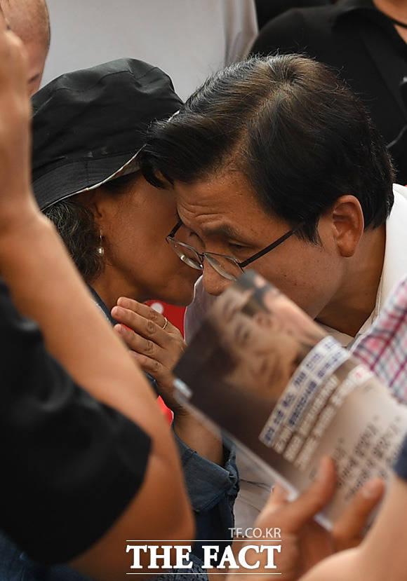 지지자와 귀엣말을 나누는 황 대표 앞으로 조국 장관 얼굴이 그려진 인쇄물이 겹쳐지고 있다.