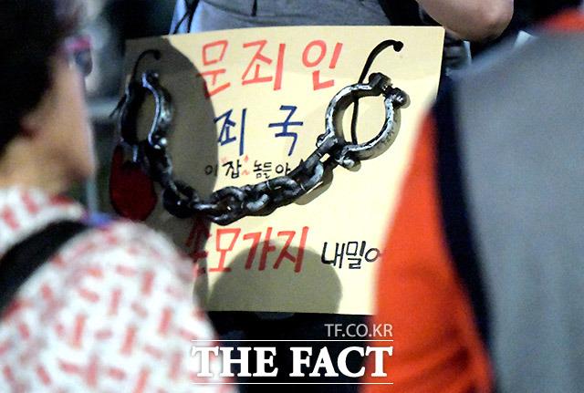 한 시위 참가자의 구호를 쓴 카드.