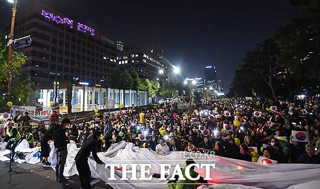 19일 오후 서울 여의도 국회 앞에서 사법적폐청산 범국민시민연대가 검찰 개혁을 촉구하는 촛불문화제를 개최한 가운데, 반대편에서 열린 반대 집회에 참가한 시민들이 건물 외벽(왼쪽 위)에 공수처 반대, 조국 구속 등의 레이저 글씨를 만들고 있다. /이새롬 기자