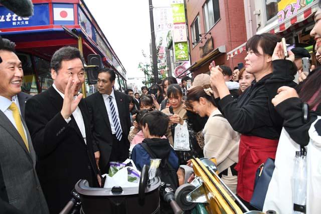 이낙연 국무총리는 24일 아베 신조 총리를 만나 면담한다. 이 총리가 22일 오후 일본 도쿄 신주쿠 신오쿠보역 거리에서 한국인 상인과 만나 손을 흔들고 있다. /이낙연 국무총리 페이스북