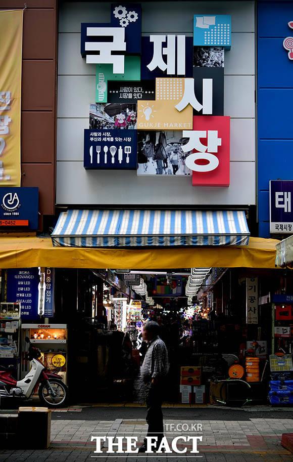 한 상인이 부산 국제시장에서 텅 빈 거리를 바라보고 있다.