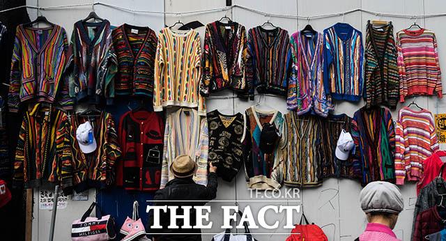 유행은 돌고 돈다 구제시장에서 한 청년이 화려한 무늬의 스웨터를 고르고 있다.