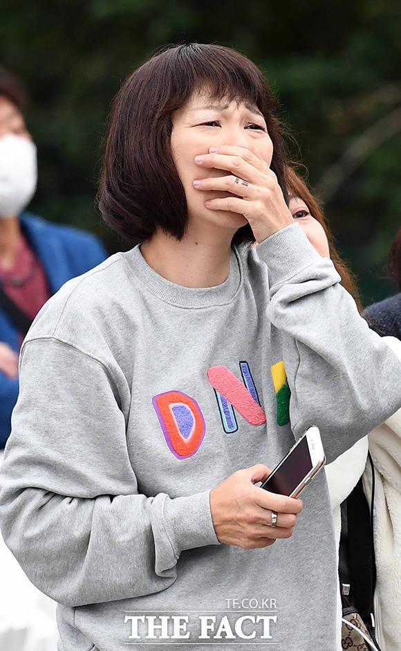 표를 구하지 못한 한 여성팬이 공연장 밖에서 팬미팅 상황을 지켜보며 울먹이고 있다.