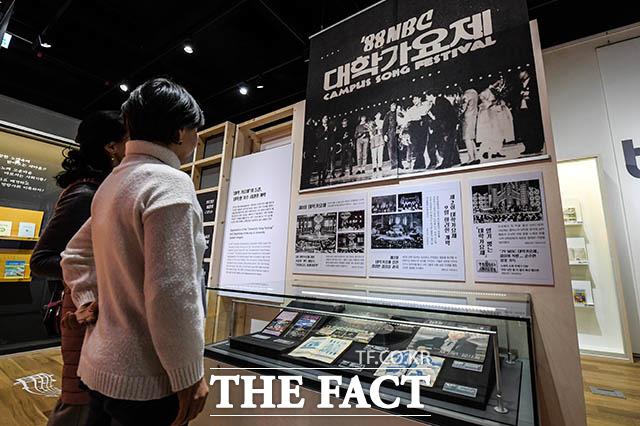 그 시절 대학가요제를 추억하며 송파책박물관에서 열린 기획 특별전시 노래책, 시대를 노래하다를 찾은 관람객들이 MBC 대학가요제 전시를 보며 추억에 잠겨 있다.
