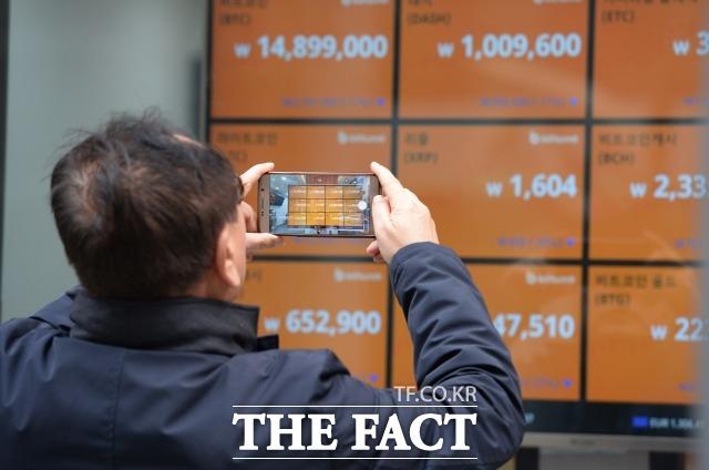 정부의 가상화폐 규제 방침에 가상화폐 가격이 폭락하고 있는 지난 2018년 1월 17일 오전 한 시민이 서울 중구 다동 가상화폐 거래소 빗썸 앞에 서 있다. /더팩트 DB