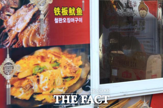 문을 닫은 음식점 창문에 마스크를 쓴 주민들의 모습이 반영되고 있다.