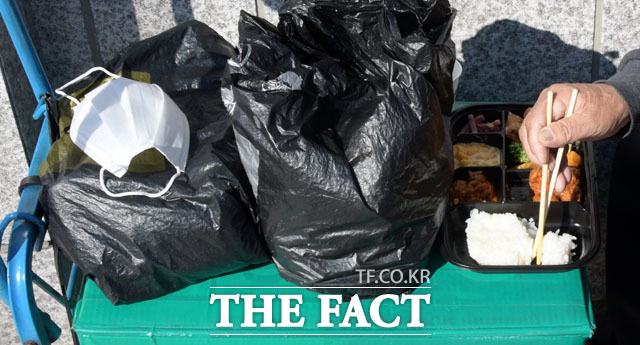 시장에서 좌판을 벌이는 한 상인이 마스크를 잠시 벗고 점심 식사를 하고 있다.