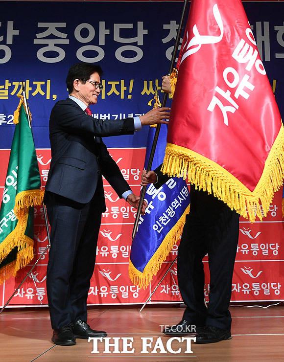 당 대표에 선출된 후 당기를 받고 있는 김문수 대표