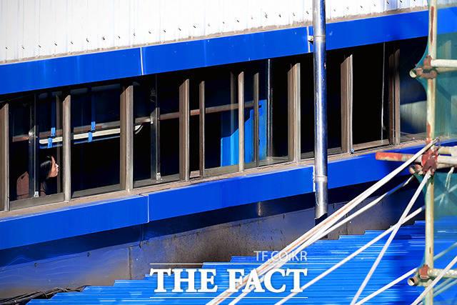 창동역 창문으로 공사현장을 바라보는 지하철 이용객