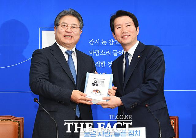 이재영 전 대외경제정책연구원장(왼쪽)에게 당규 관련 책자 선물하는 이인영 원내대표