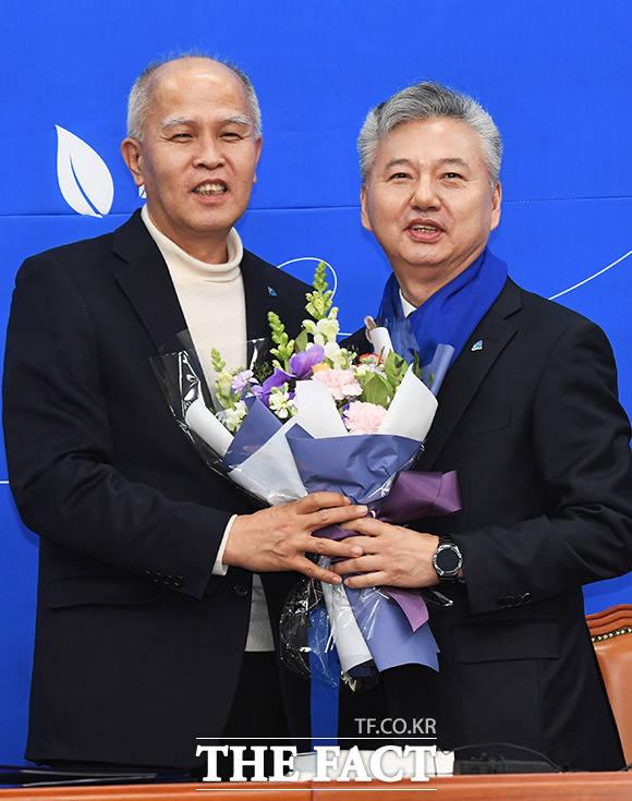 홍성국 전 미래에셋대우 대표(왼쪽)에게 꽃다발 건네는 이용우 카카오뱅크 공동대표