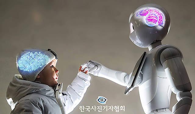 """<56회 한국보도사진상 - 최우수상> """"너처럼 똑똑하고 단단해지고 싶어."""" 아이는 마주 선 로봇의 손을 꼬옥 잡으며 새해 소망을 전했다. """"왜 나처럼 되고 싶어?"""" 로봇이 물었다. """"어려운 이웃을 돕고, 남을 괴롭히는 사람들을 혼내주는 훌륭한 사람이 될 수 있잖아. 네 소원은 뭐니?"""" 아이가 물었다. """"너처럼 따뜻한 마음을 갖고 싶어."""" 아이의 머리에는 로봇의 전자회로를, 로봇의 머리에는 인간의 뇌를 프로젝트로 투사해 촬영. <박영대, 양회성 기자/ 동아일보/ 한국사진기자협회 - 무단전재 재배포금지>"""