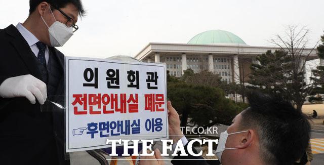 코로나19 확진자가 방문한 것으로 알려진 국회가 폐쇄됐다. 국회는 24일 오후 의원회관 2층은 통행을 금지했다. 국회 직원들이 의원회관 안내실 폐문을 알리는 문구를 붙이고 있다. /국회=이효균 기자