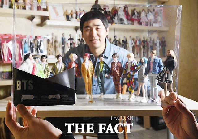 자신의 스타일로 재탄생시킨 인형들과 인형 케이스 앞에서 포즈를 취한 김태기 작가.