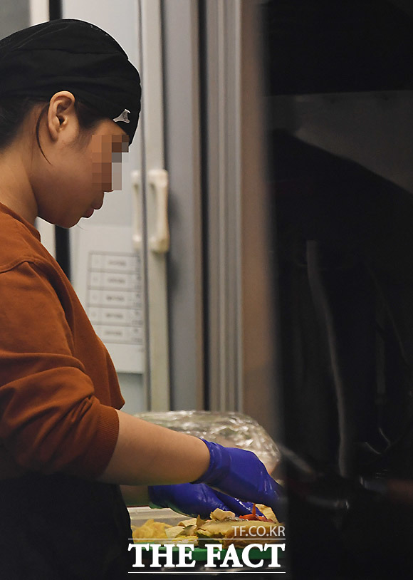 마스크를 쓰지 않은 한 종업원이 27일 오전 상암동의 한 가게에서 음식을 만들고 있다. 다수의 사람들이 먹는 음식을 만드는 사람은 더욱이 조심해야 한다.