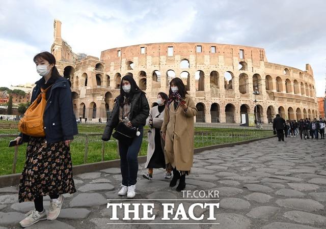 이탈리아 내 코로나19 사망자가 1만 명을 넘어섰다. 사진은 마스크를 쓴 관광객들이 이탈리아 로마의 원형경기장 콜로세움을 둘러보는 모습. /신화·뉴시스