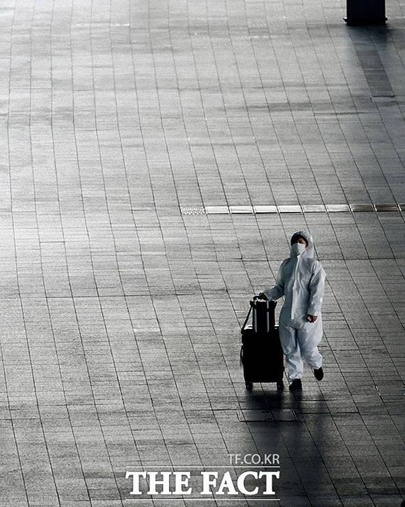 낯선 풍경 특수방호복을 입고 텅 빈 공항을 나서는 여행객.