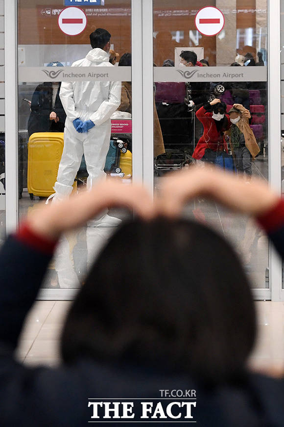 코로나19 확진자가 급증하고 있는 이탈리아의 교민들이 1일 오후 전세기를 타고 인천국제공항 제2터미널을 통해 귀국한 가운데 공항을 찾은 한 시민이 가족을 향해 하트 모양을 보이며 마음을 전달하고 있다. /인천국제공항=남용희 기자