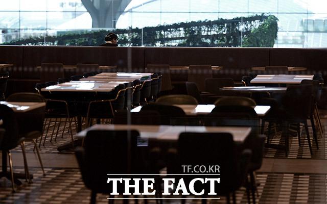 생기 잃은 공항 한 승무원이 여행객 없이 텅 빈 음식점에서 식사를 하고 있다.