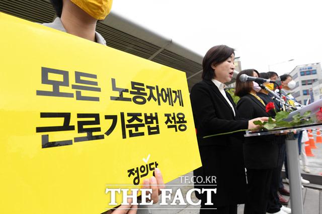 정의당이 1일 오전 서울 종로구 종로5가 전태일다리에서 130주년을 맞은 노동자의 날 기념식을 진행하고 있는 가운데 한 참석자가 평등한 근로기준법 적용을 촉구하는 문구가 적힌 피켓을 들고 있다. /임세준 기자