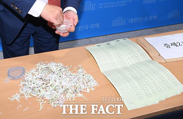 민경욱 의원이 21일 오후 국회 정론관 앞에서 파쇄된 투표용지와 구리시에서 유출된 투표용지를 공개하고 있다. /배정한 기자