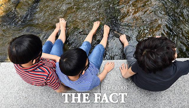서울 기온이 28도 까지 오른 30일 오후 서울 종로구 청계천에서 어린이들이 물에 발을 담그며 더위를 식히고 있다./ 이동률 기자