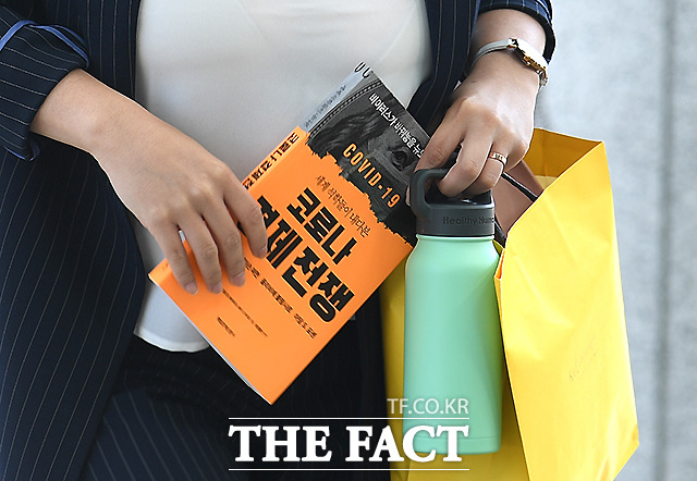 양손에는 코로나 경제전쟁 책과 텀블러