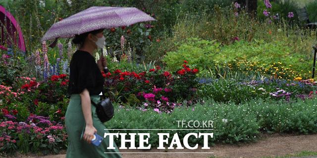 더위를 식혀줄 비가 내리는 10일 오후 서울 영등포구 여의도 공원에서 시민들이 우산을 쓰고 퇴근길에 나서고 있다. /남윤호 기자