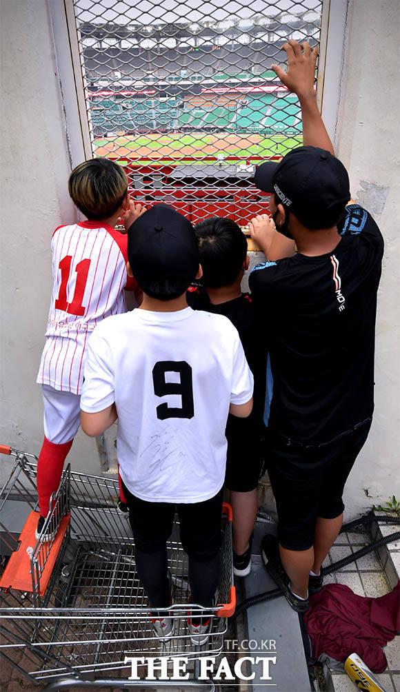 야구가 보고 싶어요…경기장 밖에서 열띤 응원 펼치는 아이들.