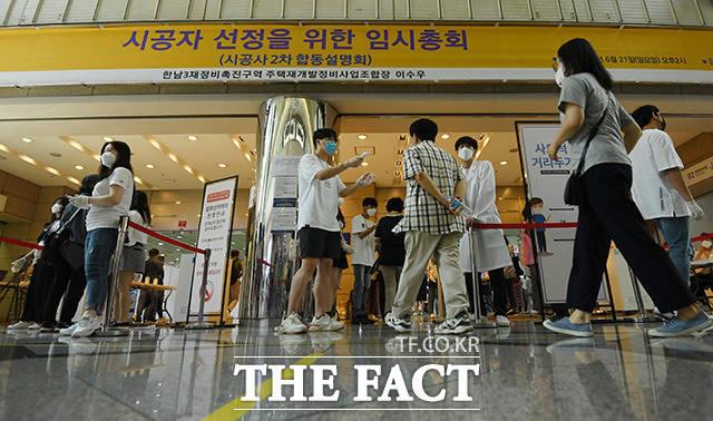 총사업비 7조 원의 역대 최대 재개발인 용산 한남3재정비촉진구역 시공자 선정을 위한 임시총회가 21일 오후 서울 강남구 코엑스에서 개최된 가운데 관계자들이 입장하며 발열 검사를 받고 있다. /남용희 기자