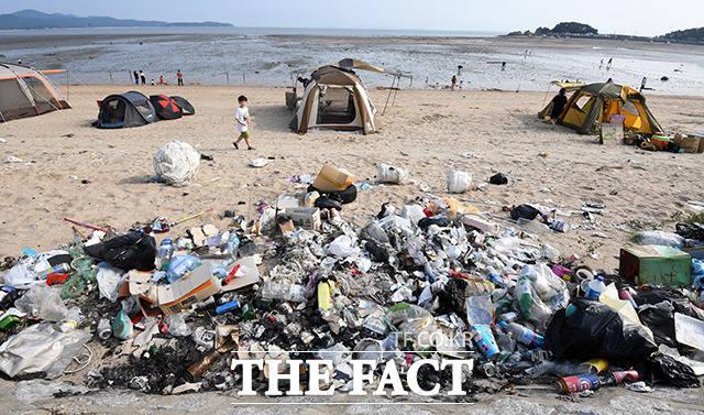 한 어린이가 쓰레기로 잔뜩 쌓인 해변을 걷고 있다.