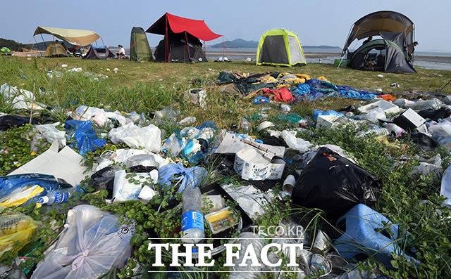 쓰레기숲 주변에 텐트를 치고 더위를 피하는 피서객들.