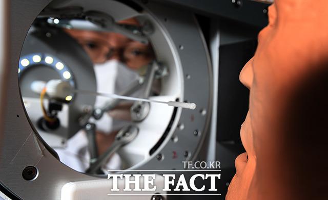 일회용 스왑(검체 채취 도구)이 환자의 비강을 통해 검체를 채취한다.