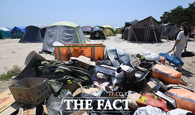 선녀바위해수욕장에서 즐기는 피서객 텐트 뒤로 쓰레기들이 쌓여 있다.
