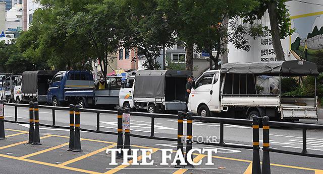 종로구 이화동의 한 도로 1차선에 여러대의 트럭이 뒷받침대를 내려 번호판을 가린 채 불법주차를 하고 있다.