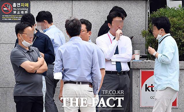 흡연자제 안내문이 부착돼 있지만, 흡연을 하고 있는 사람들.