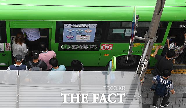 버스 앞문에 줄 지어 선 사람들에 비해 뒷문에 우르르 모인 사람들이 대조적인 모습을 보이고 있다.
