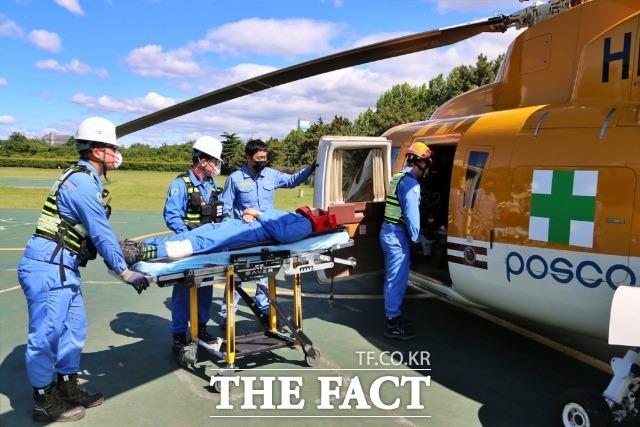 포스코가 지난 5월 20일 사내 응급의료지원 비상대응 모의훈련을 펼쳤다. 응급환자 긴급 이송을 위해 헬기로 옮기는 모습.(사진제공=포스코)