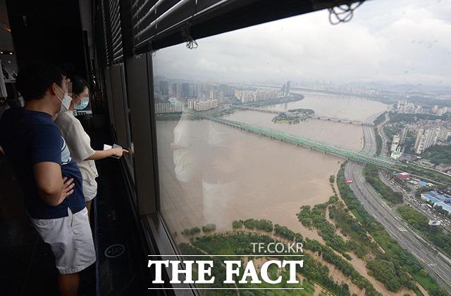 중부지방에 연일 강한 비가 내리고 있는 3일 오후 서울 영등포구 63빌딩 전망대에서 바라본 올림픽대로 일부 구간이 통제된 가운데 한 가족이 물에 잠긴 한강 산책로와 올림픽대로를 바라보고 있다. /이선화 기자