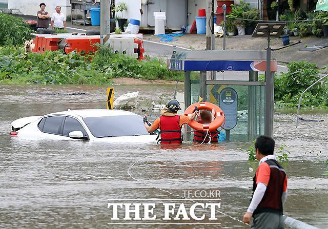 6일 경기 파주시 파평면 율곡리 일대 도로가 폭우로 인한 임진강 수위 상승으로 물에 잠긴 가운데 주행 중이던 차량이 침수되어 119 구조대원이 운전자를 구조하고 있다.  /파주=뉴시스