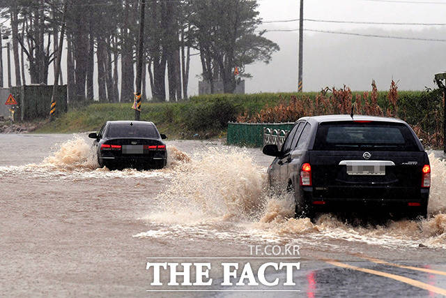 물에 잠긴 도로를 지나가는 차량들