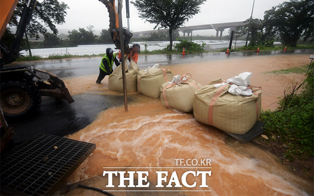 도로에 빗물 침수를 막기 위해 작업하는 관계자들