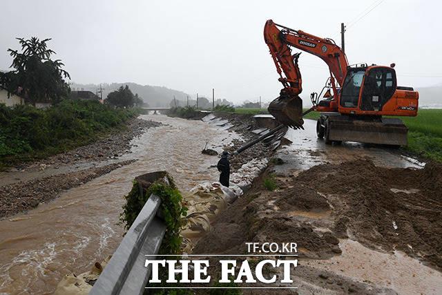 8월 3일 오후 충북 충주시 산척면 인근의 하천이 범람하며 도로가 파손돼 복구 작업을 하고 있다.