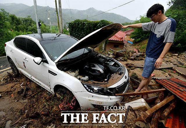 8월 3일 오전 경기 안성시 금일로의 한 주택가에서 주민이 산사태로 파손된 차량을 살펴보고 있다.